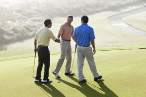 Men on golf course putting green shaking hands
